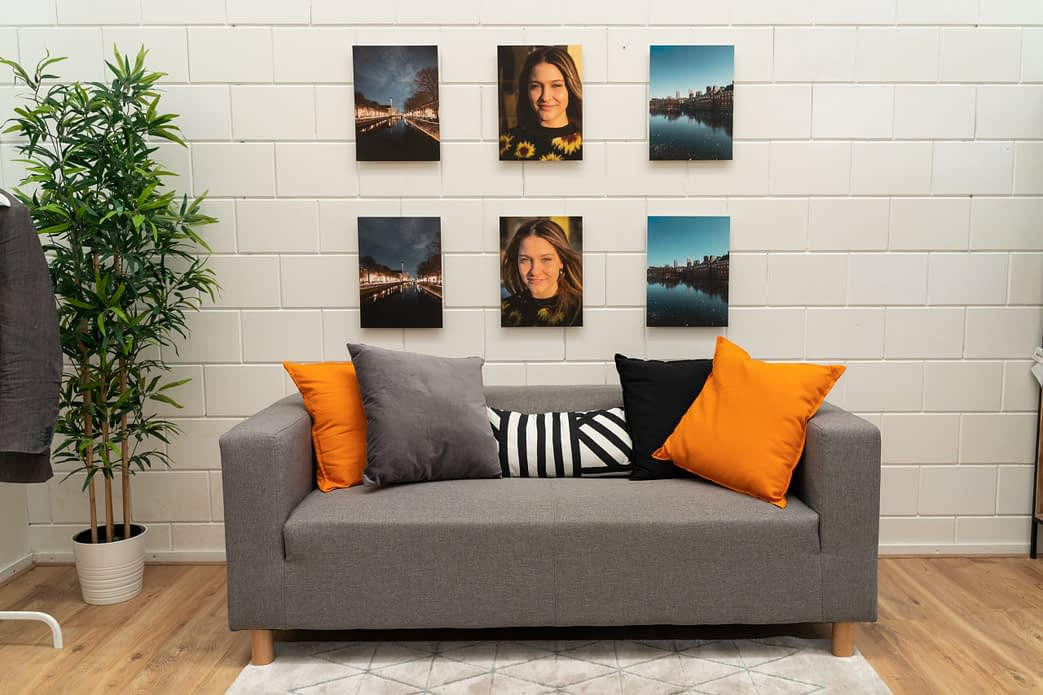 all test photos hanging on the wall, above a sofa